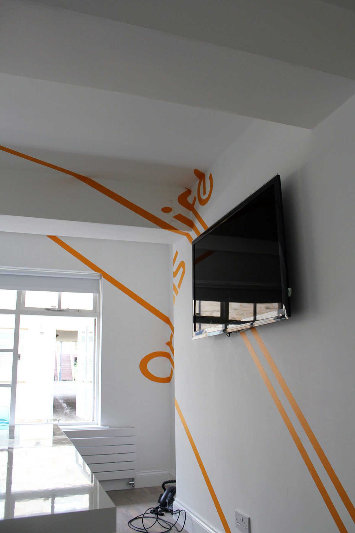 anamorphic graphics with writing on the wall and a tv