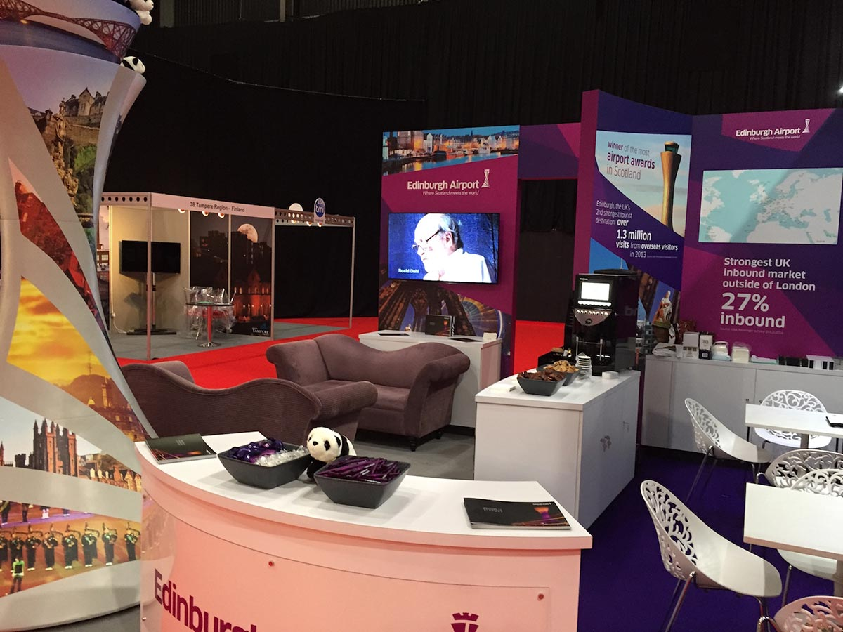 edinburgh airport exhibition stand with table/chairs, seating area and desk with a toy panda