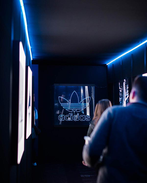 people walking down a dark corridor with led lighting with adidas branding