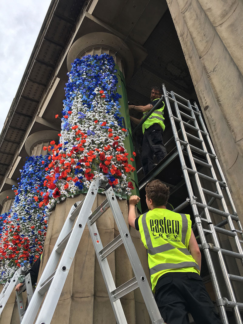 attaching flowers to the pillars at the scottish national gallery