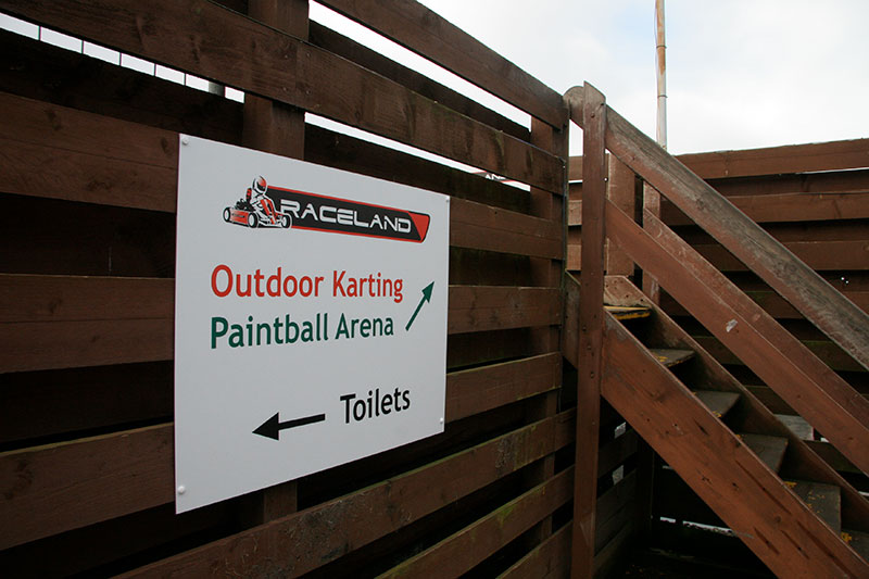 outdoor carting and paintball sign next to wooden stairs