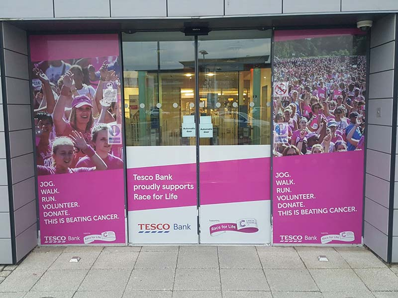 outside tesco bank with signage for beating cancer on the glass and doors
