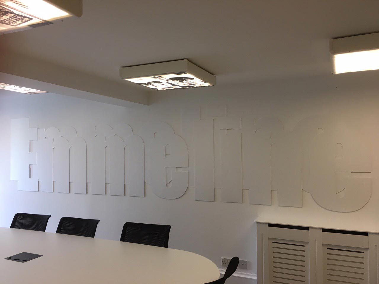 Office Interiors - meeting room with the sing emmeline on the wall