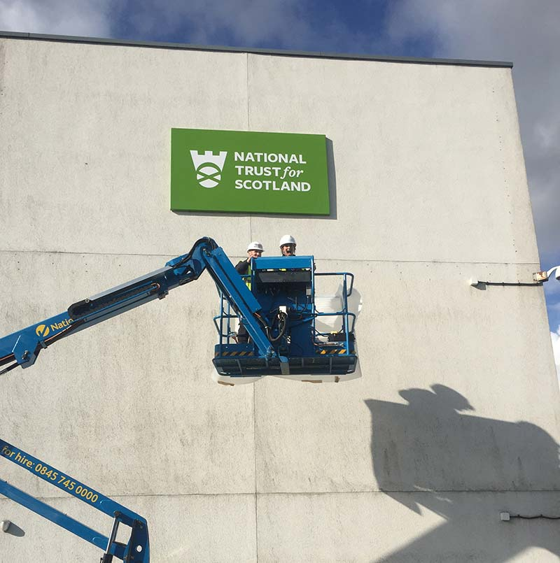 2 men up a cherry picker with national trust scotland sign in background