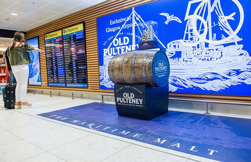 old pulteney barrel display with airport departure boards nearby