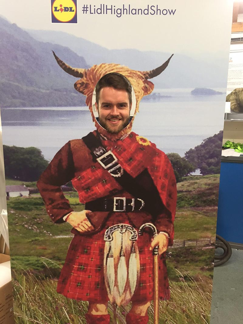 prop with highland dress and highland cow head with a cut out so a man can show his face through it