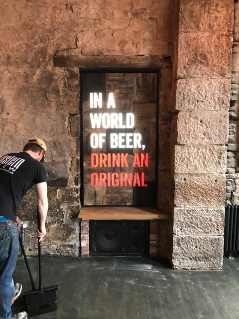 innis & gunn beer message attached to the wall with a man sweeping up in the foreground